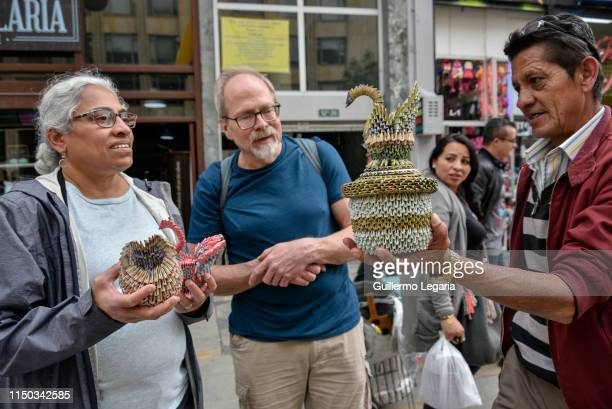 Couple of foreign tourists looks at handicrafts made with Venezuelan devalued and out of circulation banknotes Bolivares Fuertes sold by Colombian...