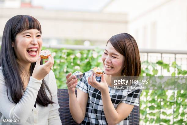 Paar freundlichen japanischen Frauen, die Süßigkeiten auf der Dachterrasse Essen