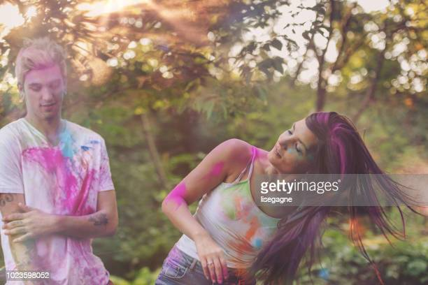 Couple of friends dancing in backyard with colored powder
