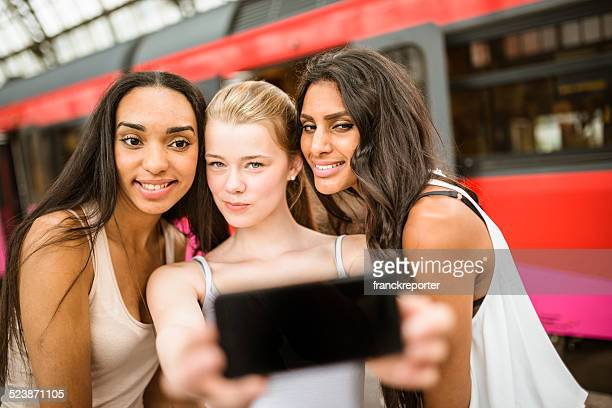 Couple of friends doing a selfie on the amsterdam station