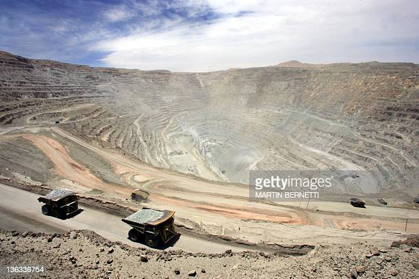 A couple of gigantic Komatsu 930 330 metric tons lorries arrive with their load at the Chuquicamata copper mine in the desert town of Calama 1000 km...