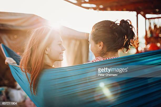Couple of girlfriends resting in a hammock