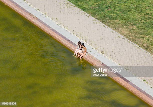 Couple of girls in bikini sitting on the pool edge on summer time cooling off