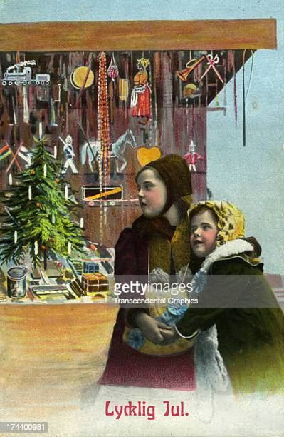 A couple of girls linger by a toy store window on this postcard published around 1910 in Boston Massacusetts