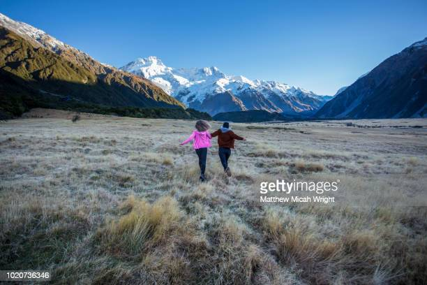 A couple of girls run through the flat plains in New Zealand's Mount Cook National Park. The snowcapped peaks can be seen in the background.