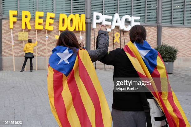 A couple of girls shake hands with Estelades Catalan separatist flag in front of 'Freedom Peace' created by Resistance Catalonia at Born plaza as a...