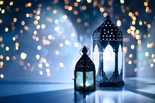 Couple of glowing Moroccan ornamental lanterns on the table. Greeting card, invitation for Muslim holy month Ramadan Kareem. Festive blue night background with glittering golden bokeh lights. 1145904609