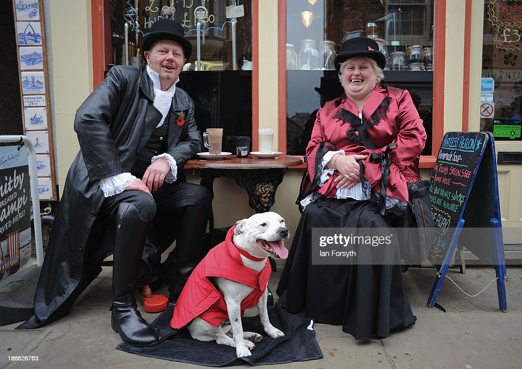 A couple of Goths pose and their dog as they relax in a cafe as they visit the Goth weekend on November 2, 2013 in Whitby, England. The Whitby Gothic Weekend that takes place in the Yorkshire seaside town twice yearly in Spring and Autumn started in 1994 and sees thousands of extravagantly dressed followers of Victoriana, Steampunk, Cybergoth and Romanticism visit to take part in celebrating Gothic culture.
