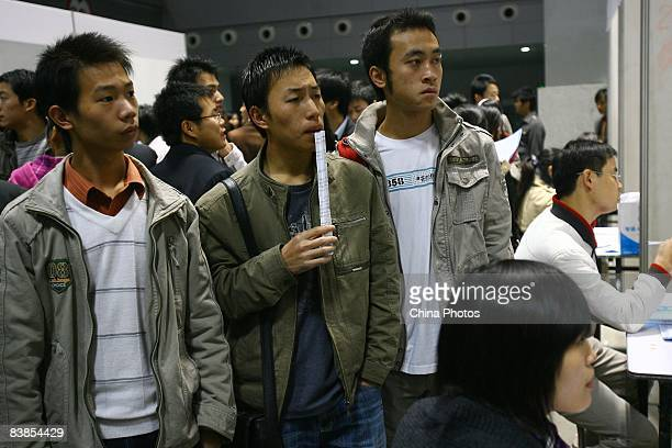A couple of graduating university students read employment information at a job fair on November 28 2008 in Chongqing China The number of Chinese...