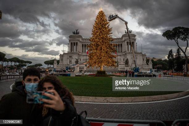 "Couple of guys take a selfie in front of the big Christmas tree so called ""Spelacchio"" at Piazza Venezia during the restrictions to contain the..."