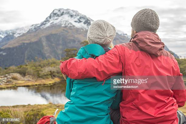 Couple of hikers contemplating mountain landscape