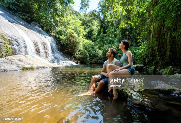 couple of hikers looking at a beautiful waterfall - brasile foto e immagini stock