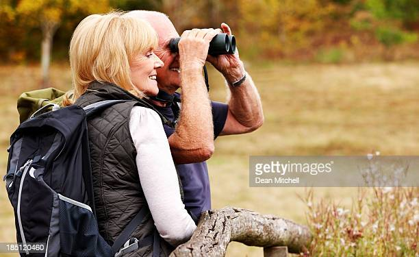 Couple of hikers looking away through binoculars
