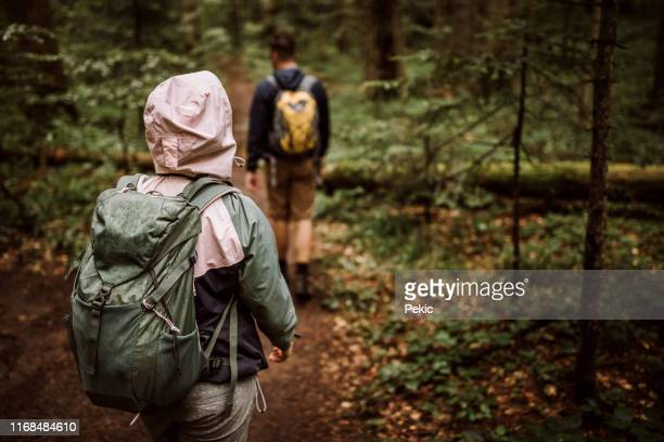 couple of hikers on their adventure in forest - following stock pictures, royalty-free photos & images