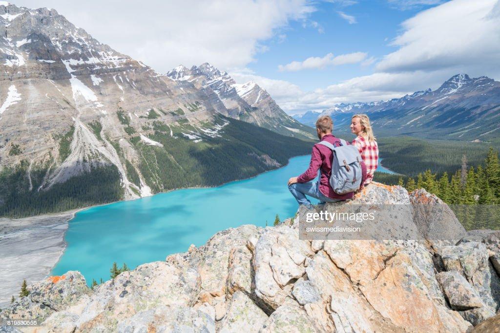 Couple of hikers overlooking mountain lake : Stock Photo