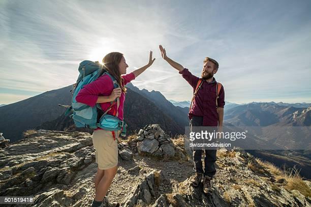 Par de hikers llega a la cima de la montaña, celebra con high five