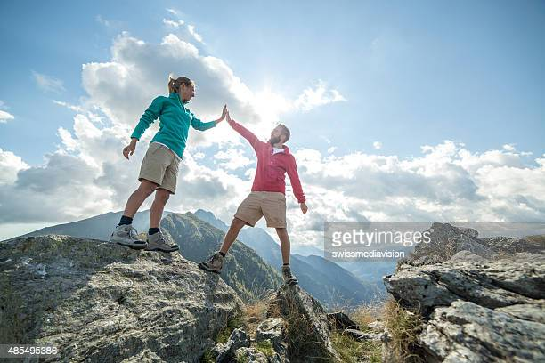 Couple of hikers reaching the mountain top celebrating