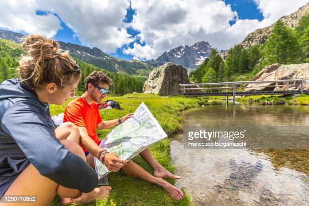 a couple of hikers reads map sitting on the grass with mountain landscape in the background. - italia stockfoto's en -beelden