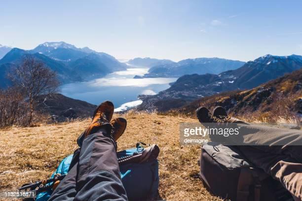 pares de caminhantes que descansam em um monte, lago no fundo - como itália - fotografias e filmes do acervo