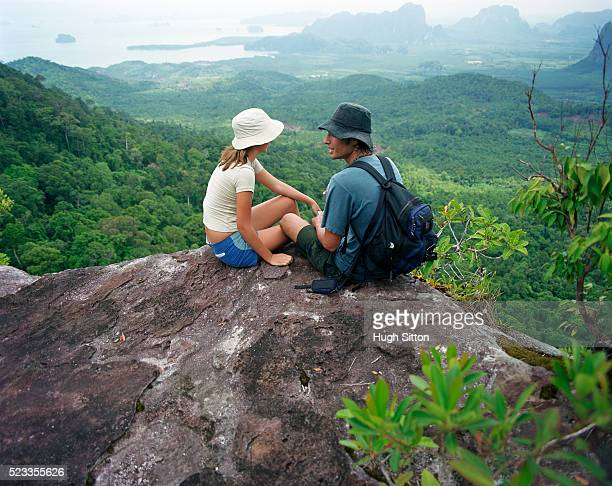 couple of hikers sitting on rocky summit, thailand - hugh sitton stock pictures, royalty-free photos & images