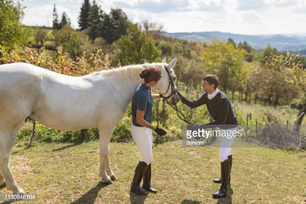 couple of horseback riders holding and stroking white horse - rein stock pictures, royalty-free photos & images