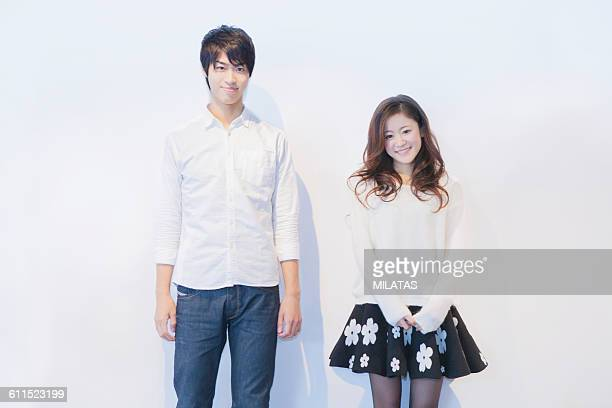 A couple of Japanese standing in front of a white wall