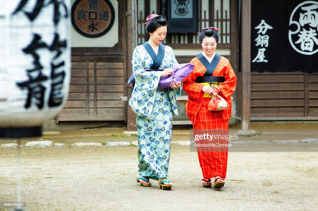 Couple of Japanese women in colorful Kimonos discussing as they walk Full length : Stock Photo