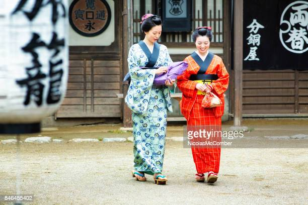couple of japanese women in colorful kimonos discussing as they walk full length - historical reenactment stock photos and pictures