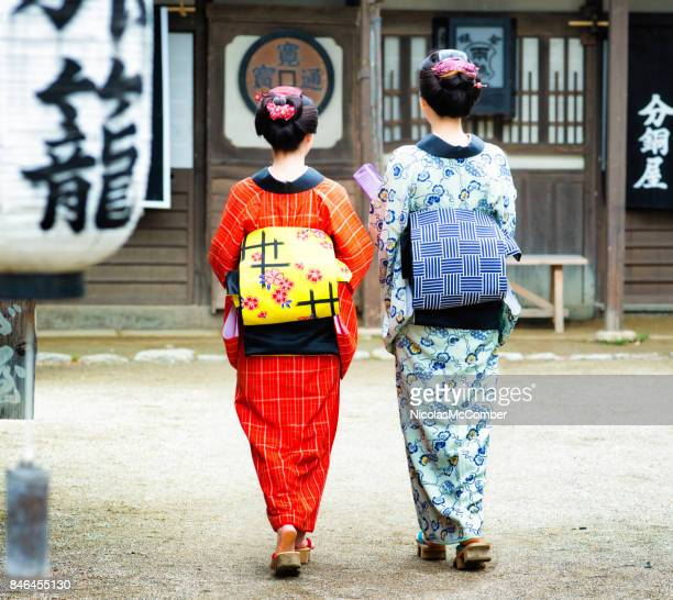 couple of japanese women in colorful kimonos with obi sash rear shot full length - obi sash stock pictures, royalty-free photos & images