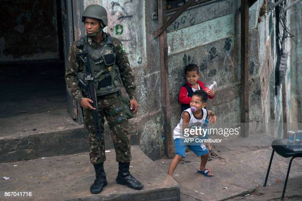 A couple of local children play next to Brazilian army soldiers during a security operation at Sao Carlos favela in Rio de Janeiro Brazil on October...