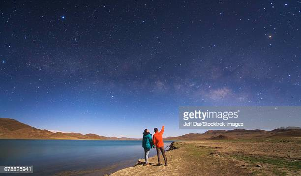 a couple of lovers enjoy a romantic moment under the milky way on a moonlit night in tibet, china. - moonlight lovers stock-fotos und bilder