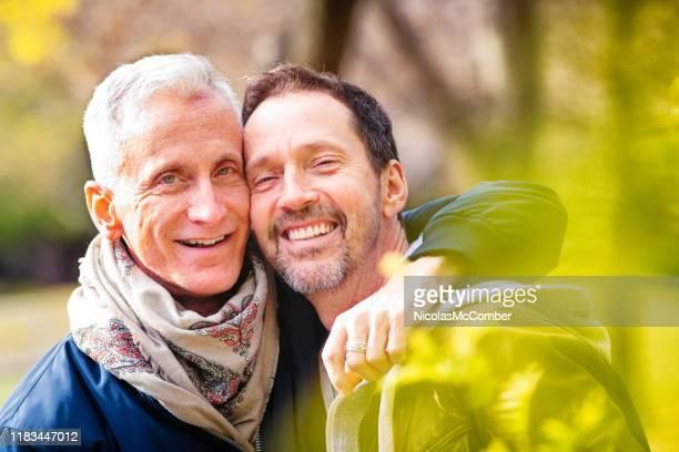 couples d'amour des hommes homosexuels aînés verticale dans un stationnement à la fin d'octobre - gay seniors photos et images de collection