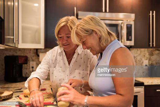 """couple of mature lgbtq women in their kitchen. - """"martine doucet"""" or martinedoucet stock pictures, royalty-free photos & images"""