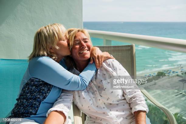 """couple of mature lgbtq women kissing on balcony over ocean. - """"martine doucet"""" or martinedoucet stock pictures, royalty-free photos & images"""