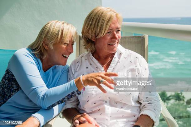 """un par de mujeres lgbtq maduras en el balcón sobre el océano. - """"martine doucet"""" or martinedoucet fotografías e imágenes de stock"""
