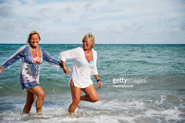 """couple of mature lgbtq women posing on the beach. - """"martine doucet"""" or martinedoucet stock pictures, royalty-free photos & images"""