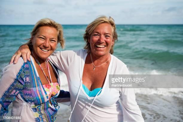 """un par de mujeres lgbtq maduras posando en la playa. - """"martine doucet"""" or martinedoucet fotografías e imágenes de stock"""