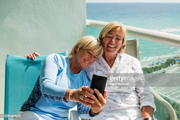 """un par de mujeres lgbtq maduras haciendo un selfie en el balcón. - """"martine doucet"""" or martinedoucet fotografías e imágenes de stock"""