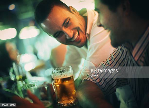 Couple of men having beer on a night out.