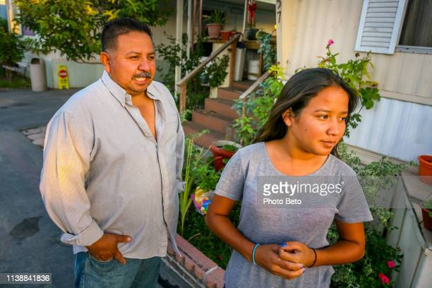 a couple of mexican immigrants in front of their home in san bernardino in southern california - migrant worker stock pictures, royalty-free photos & images