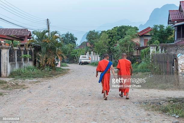 a couple of monks in orange walking on a side street in vang vieng, laos - laotian culture stock pictures, royalty-free photos & images