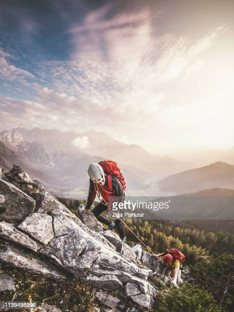 couple of mountain climbers, climbing via ferrata, a secure climbing route - mountaineering stock pictures, royalty-free photos & images