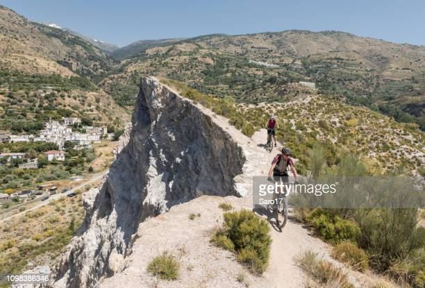 couple of mountainbikers on a single trail nearby a cliff at andalucian sierra nevada, spain. - andalucia stock pictures, royalty-free photos & images