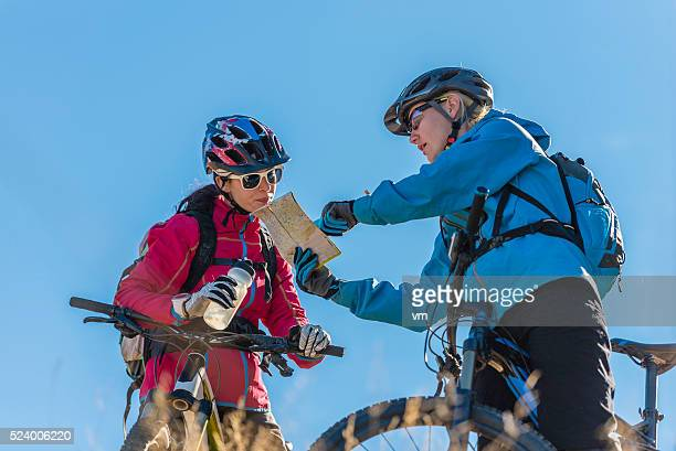 Couple of mountainbikers with map against a blue sky