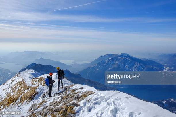 couple of mountaineers on top of the mountain ridge - lombardy stock pictures, royalty-free photos & images