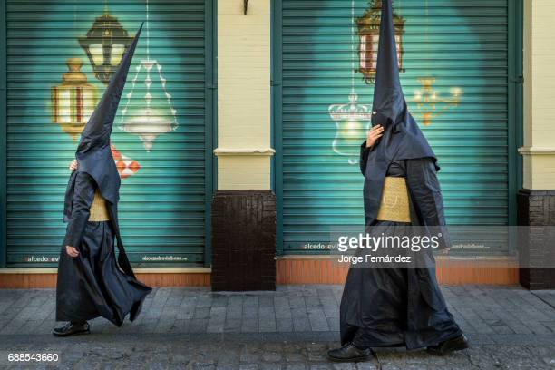 A couple of Nazarene penitents walking on the streets during Easter