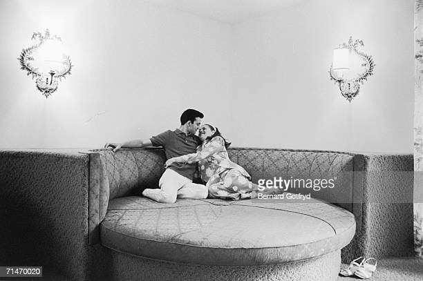 A couple of newlyweds embrace as they recline on a large round novelty bed at a hotel during their honeymoon in the Poconos Pennsylvania 1969
