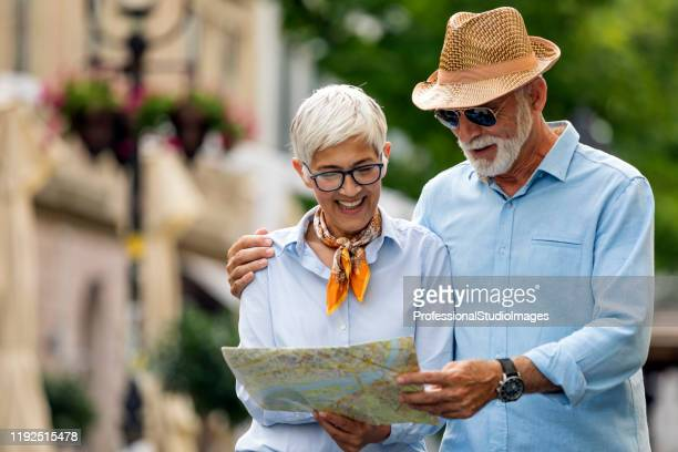 a couple of older tourists on vacation is walking through the city - studio city stock pictures, royalty-free photos & images