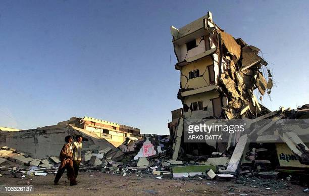 Couple of passersby look at a destroyed building 29 January 2001 where they used live in the town of Bhuj, in Gujarat state, which along with the...