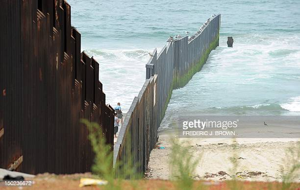 A couple of people approach the wall on Tijuanaside of the Border Field State Park fence which separates the cities of San Diego and Tijuana at the...